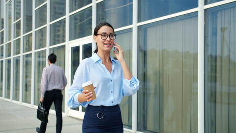 Independent woman talking on cellphone walking in city in business district Live Action