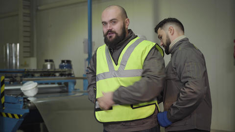 Handsome Caucasian foreman helping bearded worker to put on safety vest. Workers Live Action