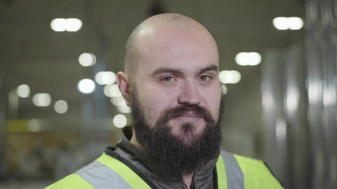 Camera moving up, portrait of bearded baldheaded Caucasian man smiling at camera Live Action