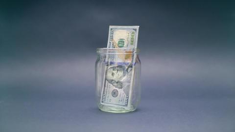 Woman Puts American Dollar 100 into a Glass Jar Footage