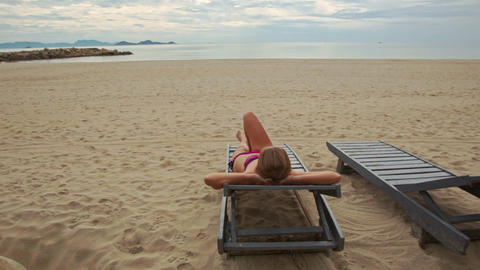 Sand Beach with Woman on Folding Chair Looks at Sea Footage