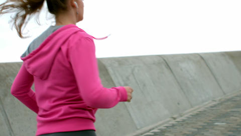 Sporty woman with headphones jogging Live Action