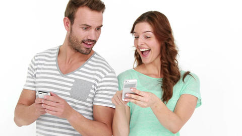Smiling couple texting and standing back to back Live Action