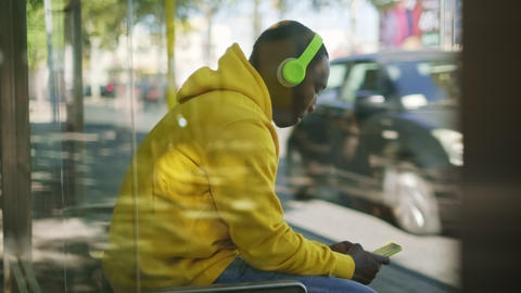 African Young Man Listening To Music At Bus Stop Live Action