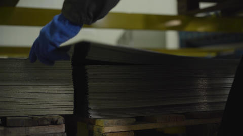 Close-up of male hands taking steel metal sheet from pile. Ready production or Live Action