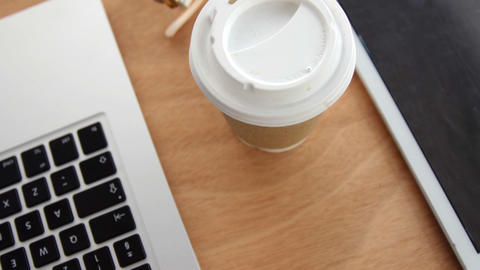 Close-up of spectacle, disposable coffee cup with laptop and digital tablet on desk Live Action