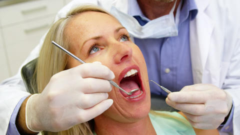 Dentist examining a female patient with dental tools Live Action