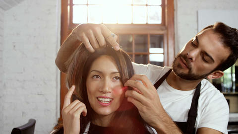 Male hairdresser styling a womans hair Live Action