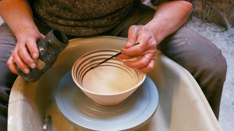 Male artist painting on earthenware bowl Live Action