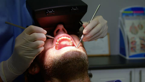 Dentist examining a male patient with dental tools Live Action