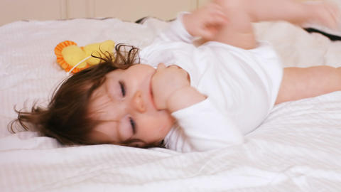 Cute baby girl playing on bed Live Action