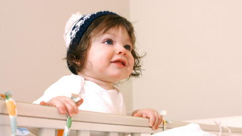 Close-up of baby girl in baby cot Live Action