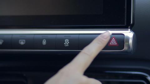 Woman pressing emergency button on car dashboard Footage