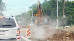 A Backhoe Works at a Road Construction Site Footage