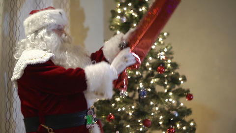 Santa Claus putting presents under the tree Footage