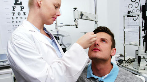 Female optometrist putting eye drop in patient eyes Live Action