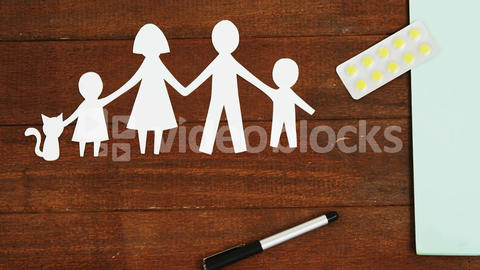 Close-up of a paper cut out of a family with tablet and pen Live Action