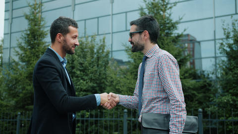 Businessmen meeting outdoors shaking hands smiling ready for partnership Live Action