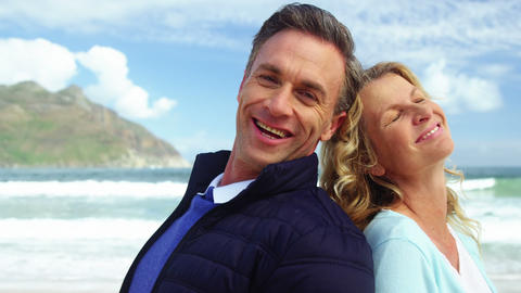 Mature couple standing back to back on beach Live Action