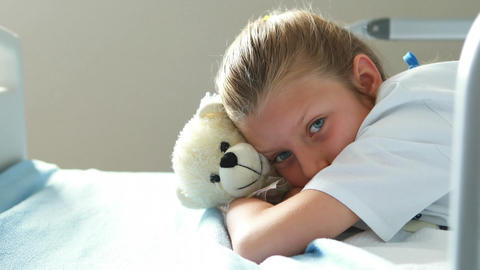 Sick girl lying with teddy bear on bed Live Action