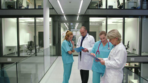 Doctors discussing over medical report in corridor Live Action