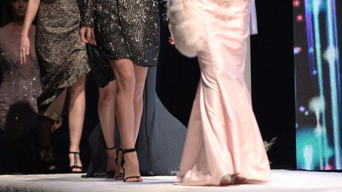 Female models walk the runway in beautiful designer dresses during a Fashion Show. Fashion catwalk Live Action
