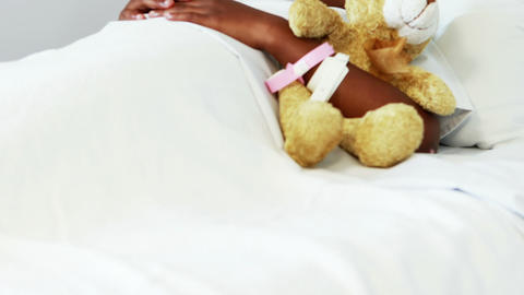 Sick girl resting with teddy bear on bed Live Action