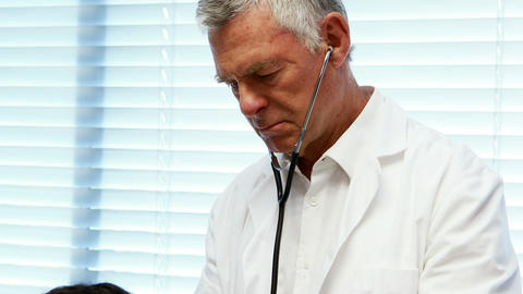 Male doctor examining a patient Live Action