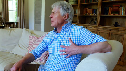 Senior man suffering from chest pain in living room Live Action