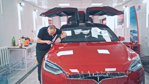 Professional applying protective film to the red Tesla car ライブ動画