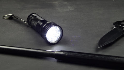Black knife baton and flashlight on a black surface Ready for a fight Live Action