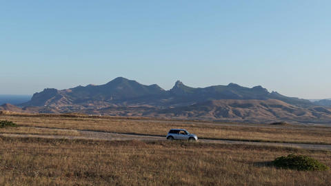 A small car rides on the road against the backdrop of the mountains Live Action