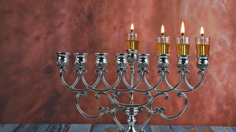 Lights candles on the third day of the Jewish holiday Hanukkah. candles are Live Action