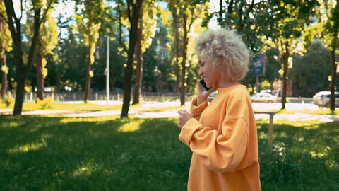 side view blonde woman has phone conversation outdoors Live Action