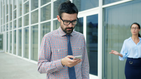 Serious banker using smartphone outdoors walking in business district alone Live Action