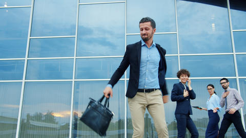 Slow motion of joyful employee dancing outdoors holding briefcase having fun Live Action