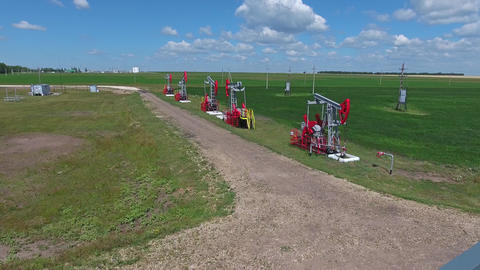 Flying over working oil pumps at sunny day, 4k Footage