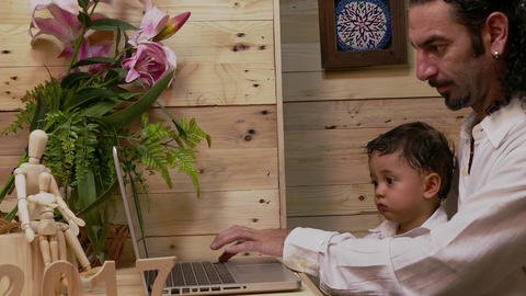 father teaching his son on laptop Footage