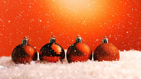 Christmas animation of glittery orange Christmas baubles placed in a row in snow 4k Animation
