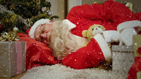 Video composition with falling snow over santa sleeping on floor next to tree Animation