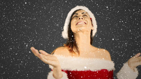 Video composition with falling snow over happy girl in santas suit showing open palms Animation