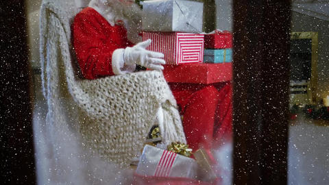 Video composition with falling snow over Santa sitting on couch in room Animation