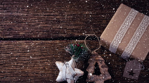 Falling snow with Christmas decorations and gift on wood Animation