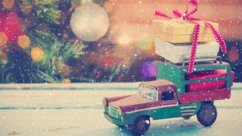 Model car with presents and blurred background of a christmas tree combined with falling snow Animation