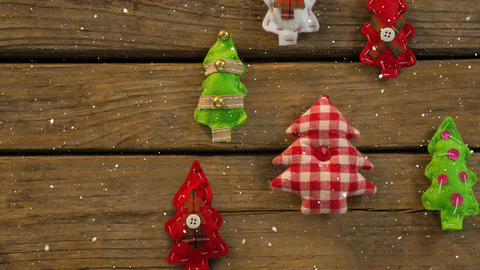 Falling snow with Christmas tree decorations on wood Animation