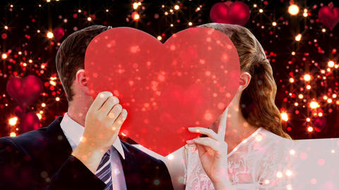 Newly weds holding big red heart in front of their faces Animation