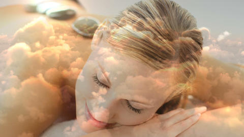 Beautiful blonde women lying at spa with hot basalt stone on the back and cloudscape for valentine d Animation