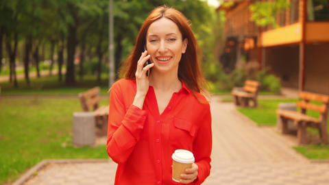 a redheaded businesswoman has a conversation by the mobile in park Live Action