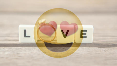 Love smiley with hearts and tiles spelling love with engagement ring for valentine day Animation