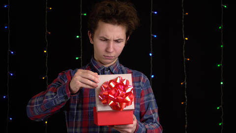 boy with a gift box on black background. gift box with ribbon for Happy New Year Live Action